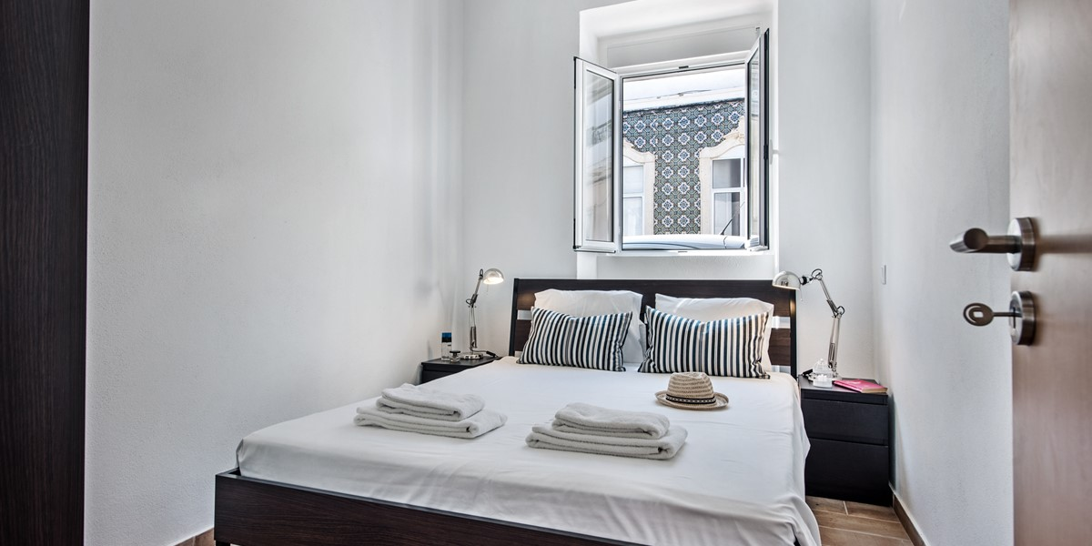 A Double Bed With Windows Looking On To A Quiet Street
